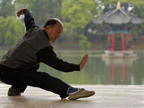 пожилой мужчина практикует тайцзицюань, стиль долгожителей