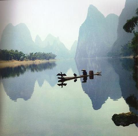 Фотография умиротворенного пейзажа: лодка плывущая по воде на фоне гор